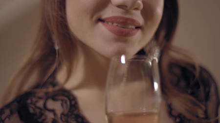 Close up shot of charming smile of the young sensual woman holding the wineglass with pink wine. Flat, prores 422 hq, slow motion