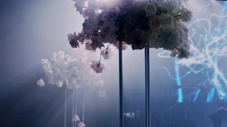 Camera rotates left to right around a wedding decorated table with wedding bouquet in tall metall vase on dark background and rays of light beaming trough smoke or haze.