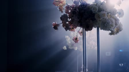 Camera rotates from right to left around a wedding decorated table with wedding bouquet in tall metall vase on dark background and rays of light beaming trough smoke or haze.
