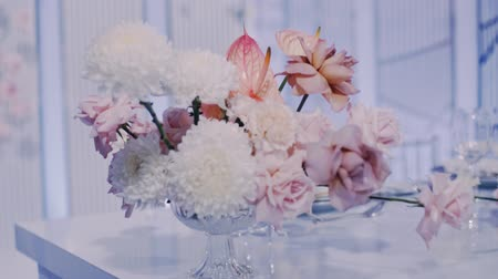 Middle parralax left to right shot of beautiful wedding decor bouquet in crystal vase on a light blue background.