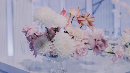 Middle parralax left to right shot of wedding bouquet in crystal vase on a light blue background. Stock mozgókép