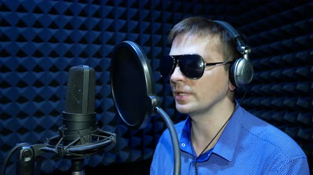 kondenzátor : Blind Man in Black Glasses Reads Braille from the White Paper Sheet and Recording a Voice or Song in the Sound Recording Studio. Blind Man Speaks with His Voice Cartoon, Movie or Promotional Movie