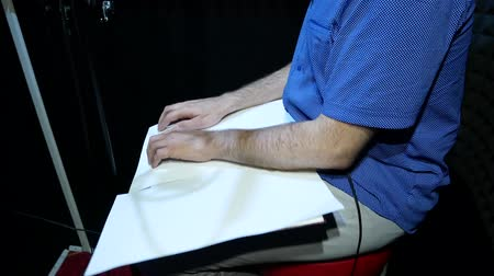 kondenzátor : Blind Man in Black Glasses and Blue Shirt Reads Braille from White Paper Sheet and Recording Voice or Song in the Sound Recording Studio For Cartoon, Movie or Promotional Movie Dostupné videozáznamy