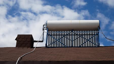 heating up metal : Solar Water Heater On The Roof Of The House On The Blue Sky Background With The Clouds. Time Laps 4k Video