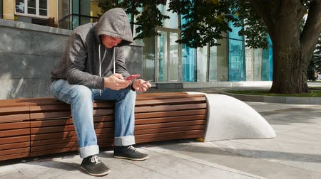fenyegetés : Hooded man holding red smartphone and credit or debit card and buy online outside near tree on a brown bench