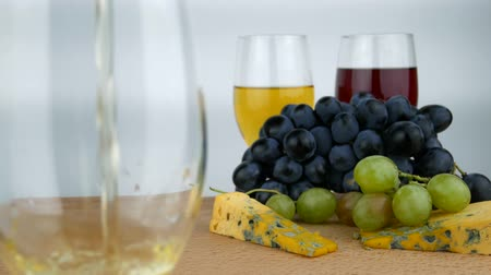 yüksek ova : White Wine Poured in Glass. Hard Cheese With Mold, White and Dark Blue Grapes. Wine Degustation on White Background Isolated Stok Video