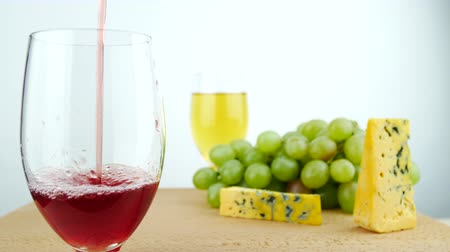 yüksek ova : Red Wine Poured in Glass On the Wooden Surface. Hard Cheese With Mold, White Grapes. Wine Degustation on White Background Isolated Stok Video