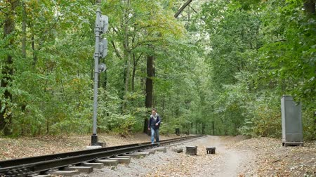 časová prodleva : Young man walks between the railway rails. A railroad station in the forest in the autumn. Student traveler with a black backpack and in a blue jacket walks away from the camera