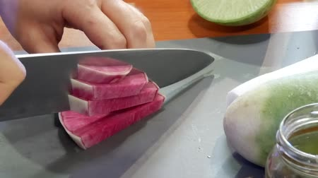 rabanete : Cutting Pink Chinese Red Meat Radish Called Watermelon Radish at Market On Kitchens Board at Restaurant or Home. Preparation for Cooking Fresh Vegetables Stock Footage