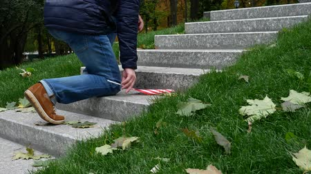 надгробная плита : Man With American USA Flag Rises on Granite Steps on Memorial with Memory Wall or Tombstone around Green Grass. Concept of Memorial Day or Veterans Day 11th November in America. Autumn, Fallen Leaves Стоковые видеозаписи