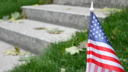 symbol of respect : Man Rises and Goes on Granite Steps on Memorial with a Memory Wall or Tombstone around Green Grass. Concept of Memorial Day or Veterans Day in America With American USA Flag