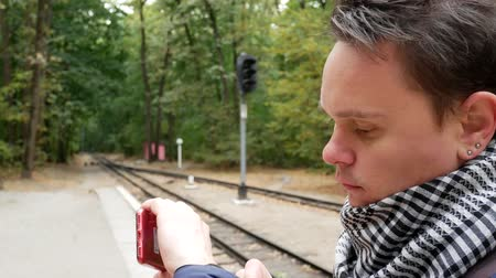 časová prodleva : A young man is waiting for train on apron and looks at a wristwatch, checking the time. A railroad station in the forest in the autumn. Student traveler is nervous because of late train