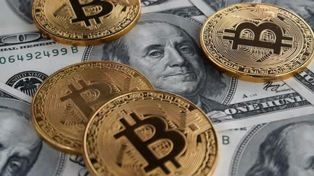 karşılaştırmak : Gold Bit Coin BTC coins rotating on bills of 100 dollars. Worldwide virtual internet cryptocurrency and digital payment system. Digital coin money crypto currency on bitcoin farm in digital cyberspace