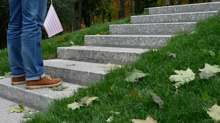 remember : Man on Granite Steps on Memorial with a Memory Wall or Tombstone around Green Grass. Concept of Memorial Day or Veterans Day in America With American USA Flag 11th November