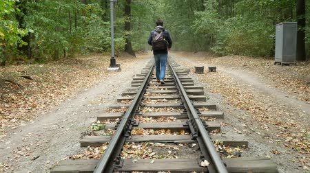 časová prodleva : Young man walks along platform between the railway rails. A railroad station in the forest in the autumn. Student traveler with a black backpack and in a blue jacket walks away from the camera Dostupné videozáznamy