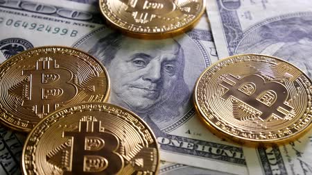 comparar : Gold Bit Coin BTC coins rotating on bills of 100 dollars. Worldwide virtual internet cryptocurrency and digital payment system. Digital coin money crypto currency on bitcoin farm in digital cyberspace