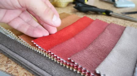 bitola : Taylor looks cotton fabric. Designing and making clothes in a textiles shop. Clothing design. Pattern construction. Tailor tools and fabrics. Fashion designer working on table Stock Footage