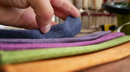 tecido : Fashion designer working on table. Taylor looks cotton fabric. Clothing design. Pattern construction. Tailor tools and fabrics. Hand of male tailor touching fabric texture in workshop studio Stock Footage