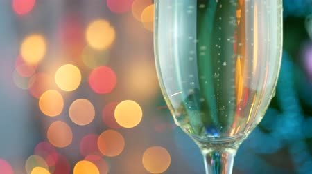 champagne flute : Champagne pour with Christmas lights into glass. Pouring wine bubbles and foaming over holiday bokeh blinking background. Success Christmas celebrating Stock Footage