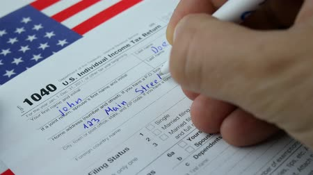 w : Man Person John Doe Is Writing Personal Information In The US Individual Income Tax Return Form 1040 in 2017 With American USA Flag Stock mozgókép