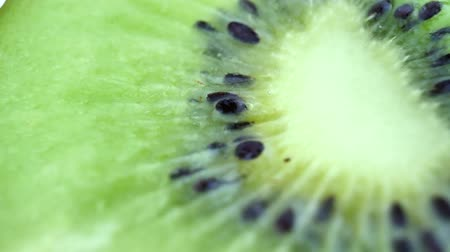 cross section : Juicy kiwi rotates as background. Macro of slice of fresh kiwi fruit isolated