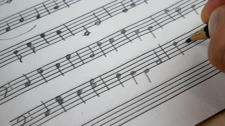 notation : Composer Comes Down a Song and Records Musical Notes Of Melody On A Paper Leaf by Pensil Stock Footage