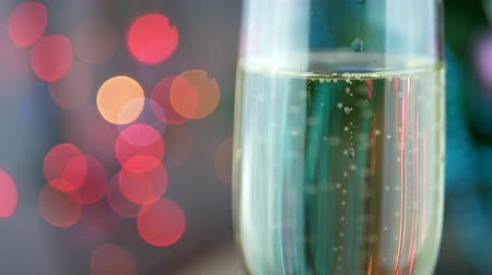 bolha : Champagne pour with Christmas lights into glass. Pouring wine bubbles and foaming over holiday bokeh blinking background. Success Christmas celebrating Stock Footage