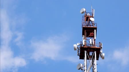 base station : Telecommunication Tower With Antennas And Repeaters Against Blue Sky And Clouds