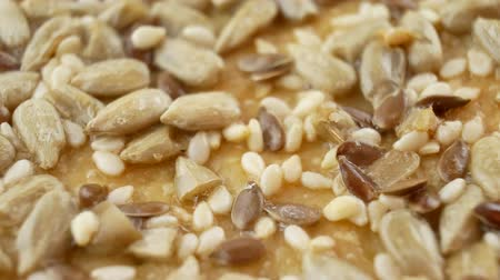 grated : Vegan crunchy cookies with sunflower, flax seeds and sesame seeds isolated. Macro view Stock Footage