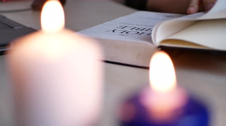 verse : Man reading and studying Holy Bible lying on the table at home with blurry candles burning Stock Footage