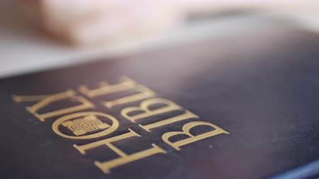 holy book : Blurry person prays with his fingers crossed near Holy Bible lying on table