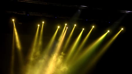 floodlight : Yellow floodlights in the smoke in the dark over the stage during the concert Stock Footage