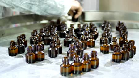 kémia : Worker in a protective gown arranges and collects glass brown bottles with liquid after conveyor on factory Stock mozgókép