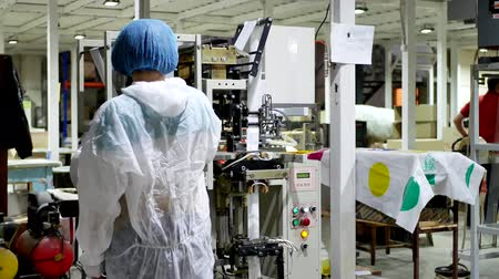packager : Employee worker woman in masked and protective gown presses buttons on control panel of machine and controls packaging machine for packing any powders on factory