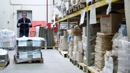 stockpile : Warehouse worker driver in uniform moving cardboard boxes by forklift stacker loader. Manual forklift pallet with boxes in large modern warehouse