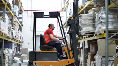 stockpile : Warehouse worker driver in uniform moving cardboard boxes by forklift stacker loader. Forklift pallet with boxes in large modern warehouse