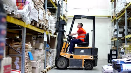 stockpile : Forklift pallet with boxes in large modern warehouse. Warehouse worker driver in uniform moving cardboard boxes by forklift stacker loader Stock Footage