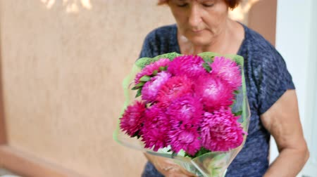 michaelmas daisy : Elderly woman florist makes a bouquet with michaelmas daisy or aster flower on table for flower shop