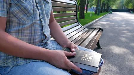 bible study : Man is holding a Holy Bible in his hand sitting on a bench in a park in the summer on a sunny day