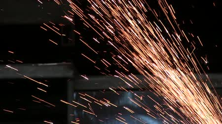spawacz : Industry worker cutting metal with grinder. Glowing sparks at metal sawing