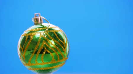 enforcamento : Decorated green Christmas balls spinning on a blue background with copyspace foe text