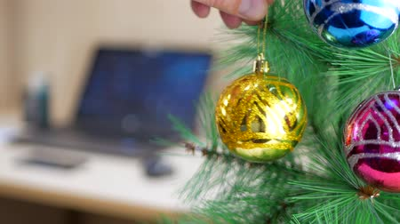cicili bicili : Businessman hanging gold or yellow Christmas ball on a Christmas tree in office at work place background Stok Video