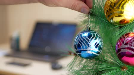 мишура : Clerk hanging blue Christmas ball on a Christmas tree at work place with notebook background Стоковые видеозаписи