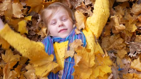 throwing in : Smiling happy little girl lying and tossing or throwing fallen leaf in autumn in park