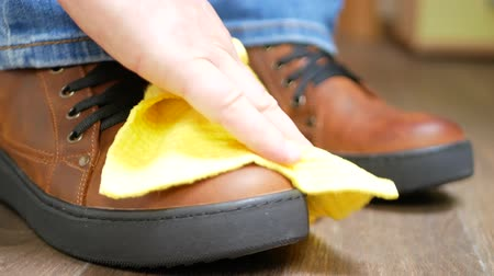 camurça : Hand dusting brown leather shoes with a yellow rag from dust and dirt
