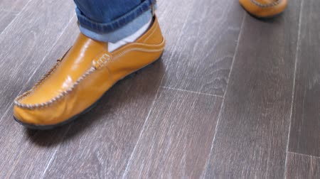 szewc : Man shining orange leather shoes with a yellow rag