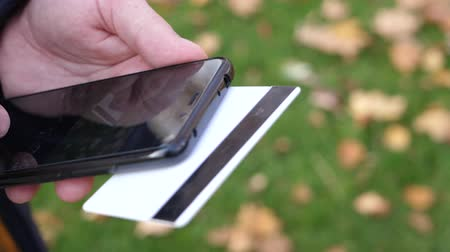 pátek : Man hands holding a credit card and using smart phone for online shopping on a background of green grass with yellow fallen leaves in autumn Dostupné videozáznamy