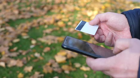 monção : Man using mobile smartphone and credit card on a background of green grass with yellow fallen leaves in autumn. Shopping online concept Stock Footage