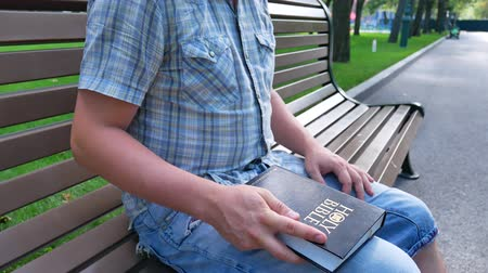 verse : Man is holding a Holy Bible in his hand sitting on a bench in a park in the summer on a sunny day