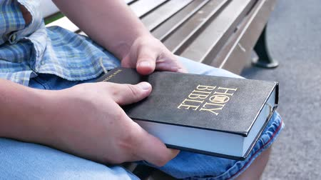 holy book : The person prays with his fingers crossed with the Holy Bible sitting on a bench in a park in the summer on a sunny day Stock Footage